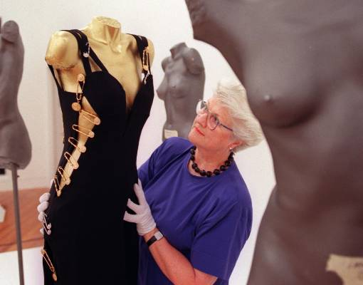 A dress infamously worn by British model Elizabeth Hurley is adjusted by Te Papa textile conservator Valerie Carson in 2003.