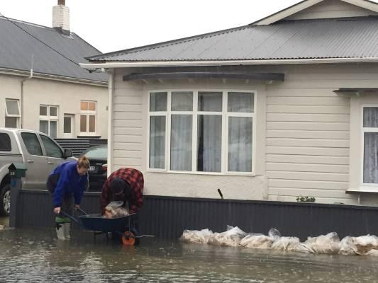 Residents of Richmond St in Dunedin sandbag their homes.