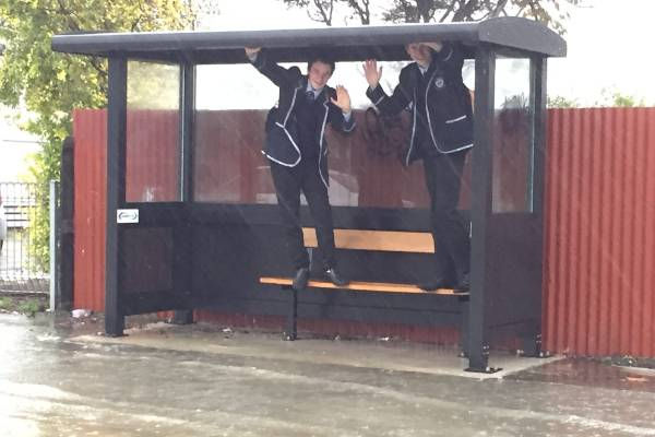 Schoolboys try to keep dry amid the flooding.
