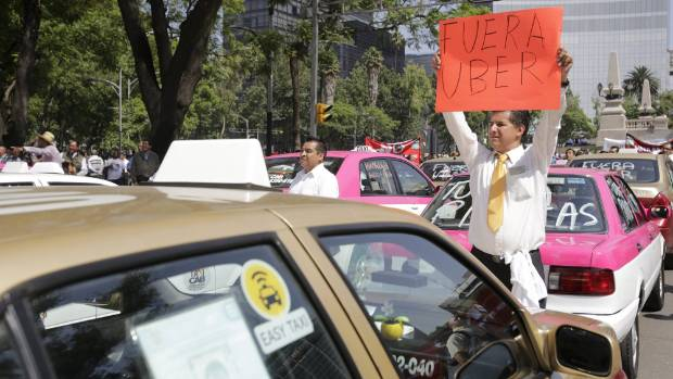 "A local taxi driver holds up a placard reading ""Uber out"" during a protest in Mexico City in May 2015."