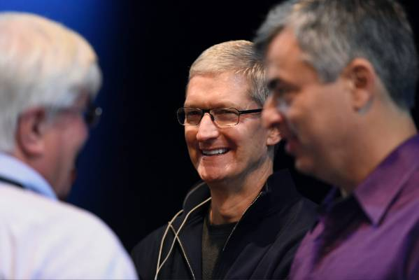 Apple CEO Tim Cook speaks with Ron Conway, founder of SV Angel, and Eddy Cue, senior vice president of Internet Software ...