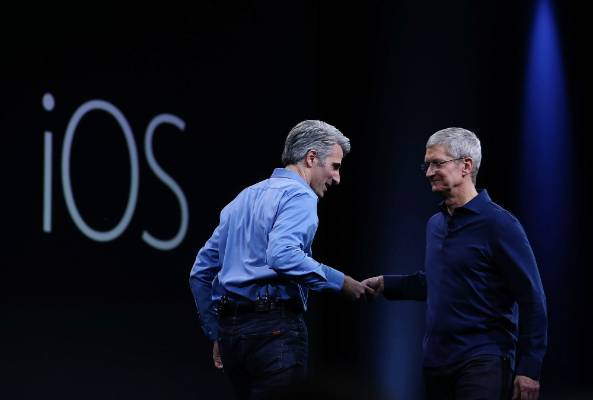 Apple senior vice president of Software Engineering, Craig Federighi, shakes hands with Tim Cook during WWDC15.