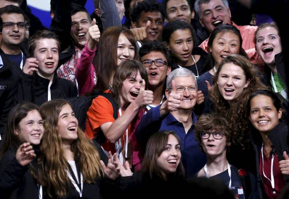 Apple CEO Tim Cook poses with scholarship winners following his keynote address at the Worldwide Developers Conference ...