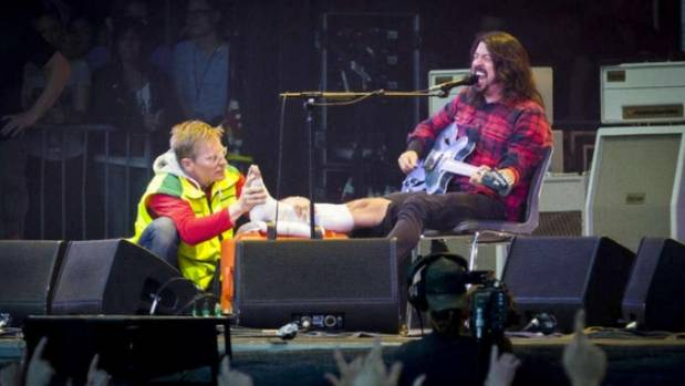 Dave Grohl carries on with a Foo Fighters concert as a paramedic tends to his injured leg.