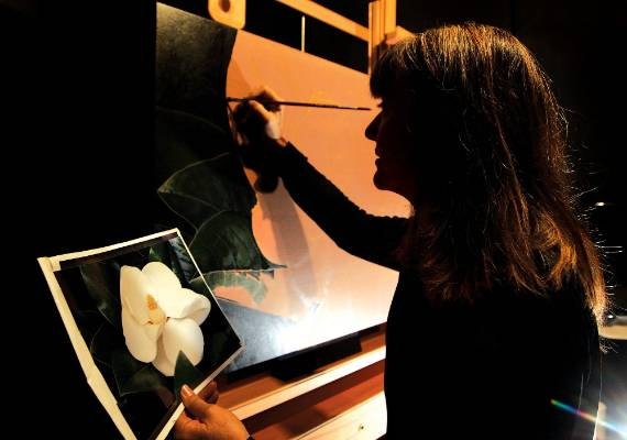 Amanda paints in an all-black room with bright lights to illuminate her picture of what will be a magnolia grandiflora.