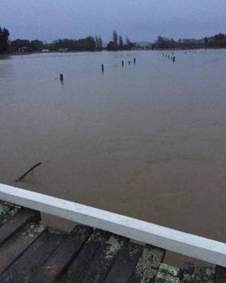 Water nearly laps at the top of fence posts on Te Matai Rd, Palmerston North.