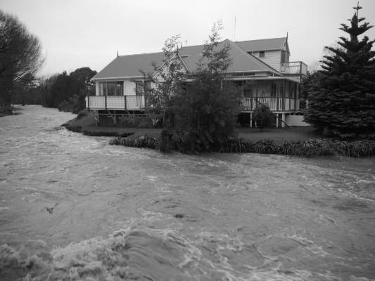 Black and white photos of flooding outside a house in Feilding.