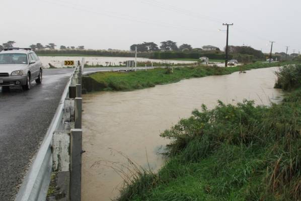 Cars drive through the flood waters as the Mangaone Stream bursts its banks on Te Horo Beach Road.