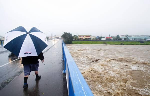 Waitara River floods comes up floods over Waitara Bridge.
