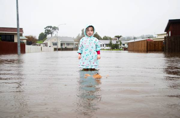 Shyanne Donghi-Johnson, 3 and a half plays on her flooded street in Waitara Makere Street where residents are unable to ...