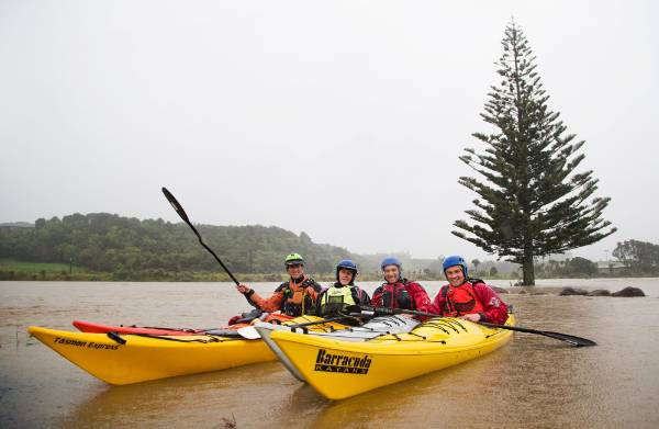 Coming in from some mad fun on their kayaks in the Waitara river.  From left Kayakers   Peter Vanlith, Tony Gable, James ...