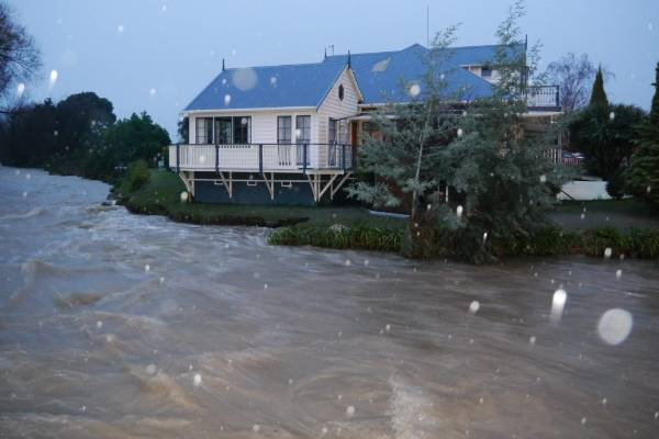 A swollen river rushes past a house in Feilding.