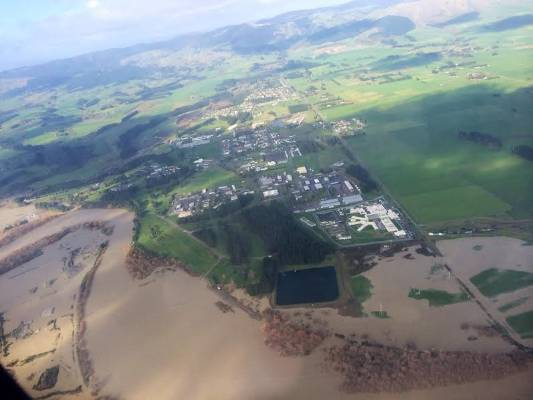 The swollen Manawatu River has burst onto farm land.