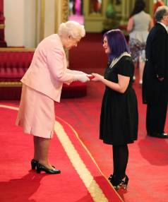 The Queen presents Tabby Besley with a Queen's Young Leader Award at Buckingham Palace.