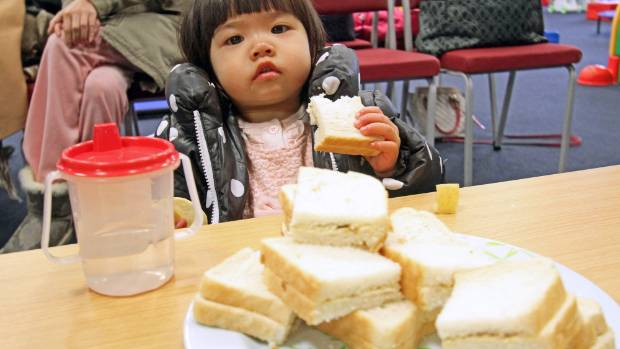 Natasha Zhang, 20 months, enjoys sandwiches at the Salvation Army office in Lower Hutt.The bread was donated by Goodman ...