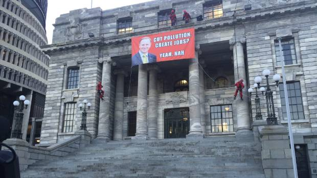 Two of the four protesters who climbed Parliament descend from the roof late on Thursday afternoon