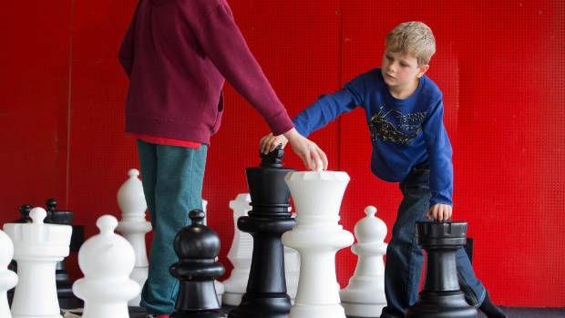 J.T Byrne, 8 and Ben Bron, 7, figure try to out wit each other in a game of giant chess during the school holidays.