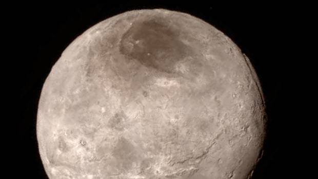 Scientists are debating the dark spot on Pluto's moon, Charon.