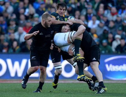 Eben Etzebeth of South Africa gets tackled by All Blacks hooker Dane Coles.