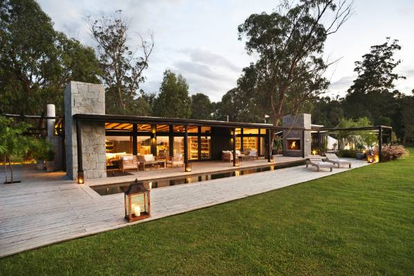 The home of Geoff and Sarah Cone, with its black-stained timber, stone and glass, blends neatly into the Uruguayan landscape