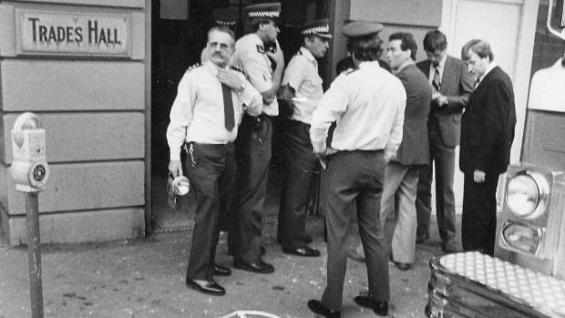 Uniformed and plainclothed policemen  outside the front door of the Trades Hall in Vivian St, Wellington. Shattered ...