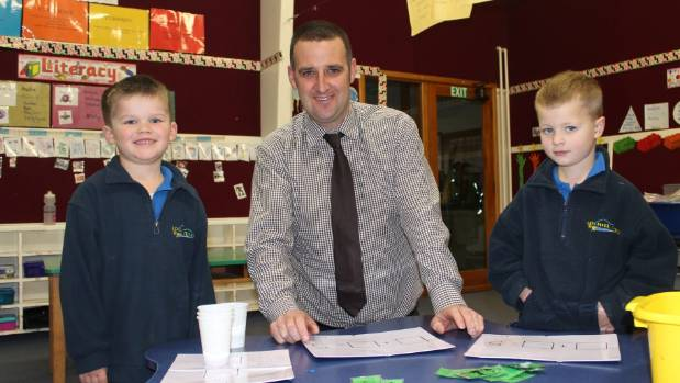 Lochiel School's new principal Geoff Folster works with 5-year-olds Ben Robson and Hunter Rhodes. Folster has joined the ...