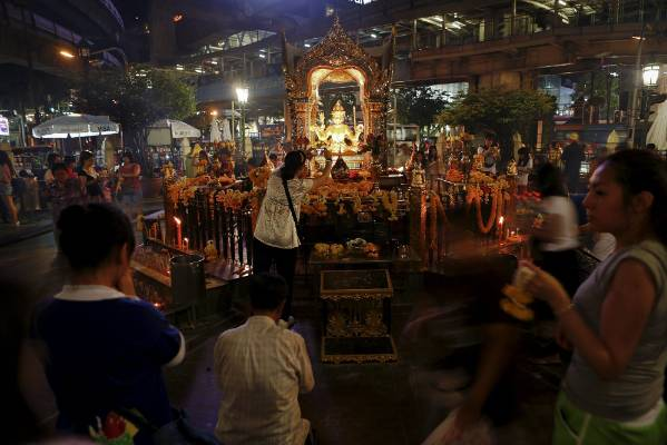 People pray at the famous San Phra Phrom shrine, known as the Erawan shrine in English, of the Hindu god Brahma, in ...