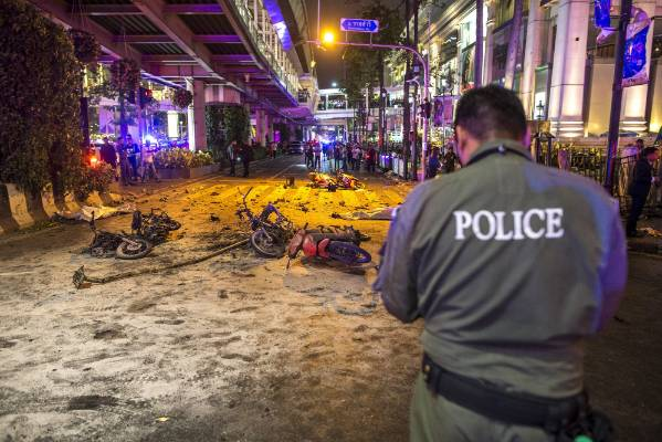 Bodies of victims are covered with white sheet among wreckage of motorcycles and other debris as security forces and ...