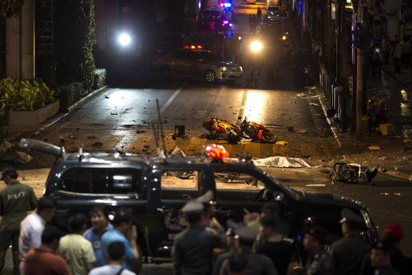 The body of a victim is covered with white sheet as security forces and emergency workers gather at the scene of the ...