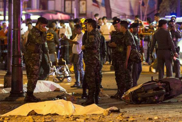 Bodies of victims are covered with white sheet as security forces and emergency workers gather at the scene of the blast ...