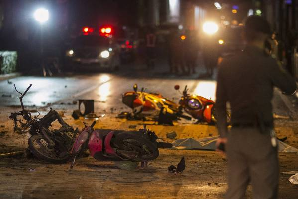 Bodies of victims are covered with white sheet among wreckages of motorcycles and other debris as security forces and ...
