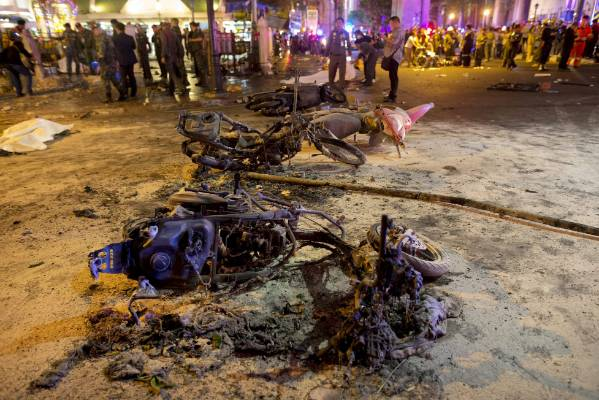 Wreckage of motorcycles are seen as security forces and emergency workers gather at the scene of a blast in central Bangkok.