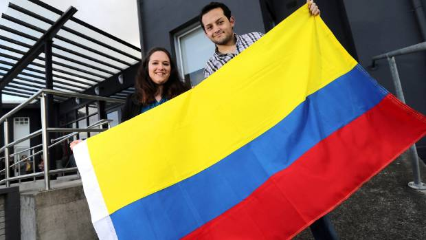 Govett Quilliam's Lisa Wansbrough hands over a Colombian flag to ITL employee Juan Gutierrez. ITL had five flags stolen ...
