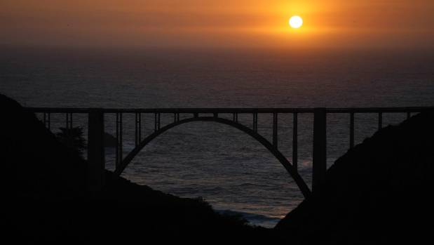 The sun sets over the Pacific Ocean behind Bixby Bridge.