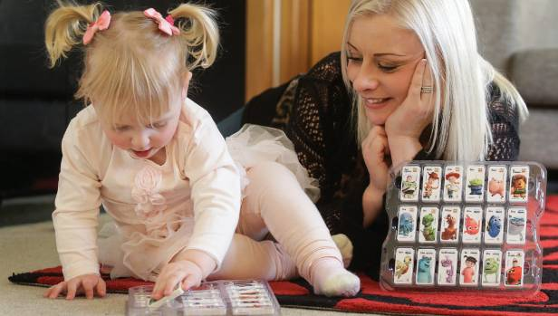 Deanna Sigmund and 1-year-old daughter Ashley play with their collection of Countdown Domino Stars.