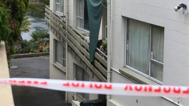 Police tape off an area of flats on Victoria St after a stabbing.