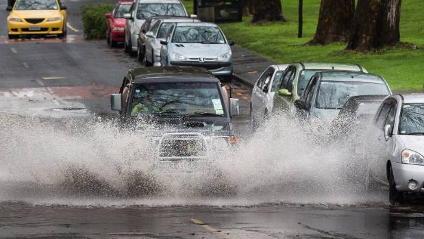 A 4WD makes a splash as it drives through flooding at the bottom of Howe Street in Auckland city.