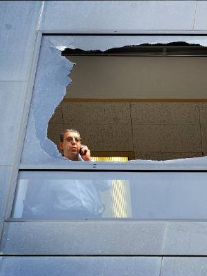 A man looks out the broken window at 1 Willis St in 2002 when it was the BNZ Tower.