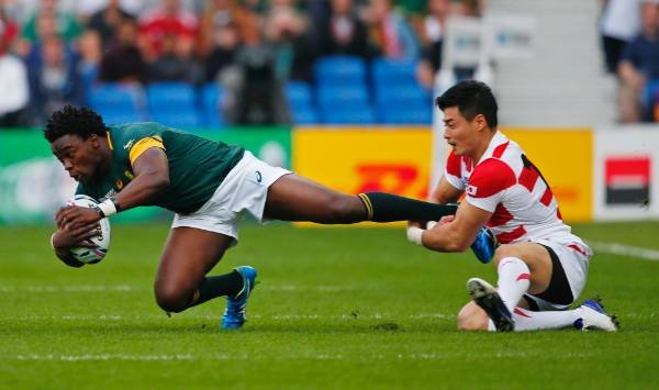 South Africa's Lwazi Mvovo is tackled by Japan's Akihito Yamada.