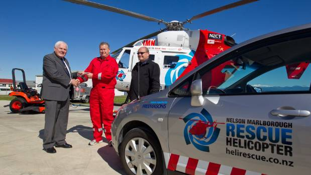 Nelson Marlborough Rescue Helicopter chief pilot Tim Douglas-Clifford, centre, is presented with a donated rapid ...