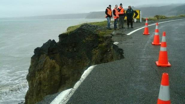 Council roading contractors contemplate the damage caused to Cape Palliser Road in south Wairarapa by heavy rain overnight.