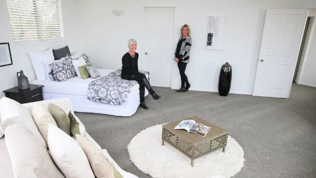 Staging stylist Nicohla Waugh and Tiffany Corbett stand in a room they staged from scratch.