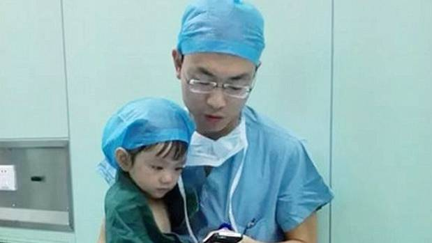 The Touching Moment Chinese Surgeon Calms Yearold Girl About To - Surgeon calms crying 2 year old girl about to undergo heart surgery with cartoons on his phone