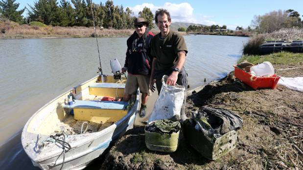 Garth Haylock, left, helps clean up the Opawa River, in Blenheim, with Driftwood Retreat and Eco-Tours owner Will Parsons