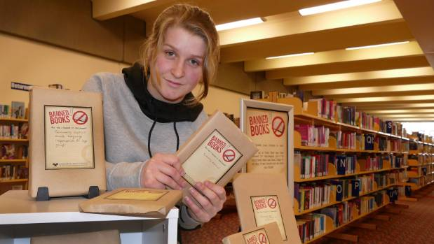 Teen librarian Rowan Kiff arranges a display of banned book at the Invercargill Public Library.