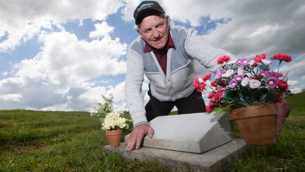 Maurie Zinsli, project restoration manager for Tokanui Hospital Cemetery brushes up a mounted headstone that will hold a ...