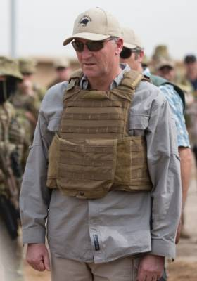 Prime Minister John Key wears a flak jacket as he talks with Iraqi troops and New Zealand trainers.