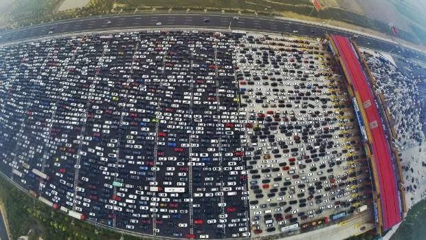 Vehicles are stuck in a traffic jam near a toll station as people return home at the end of a week-long national day ...
