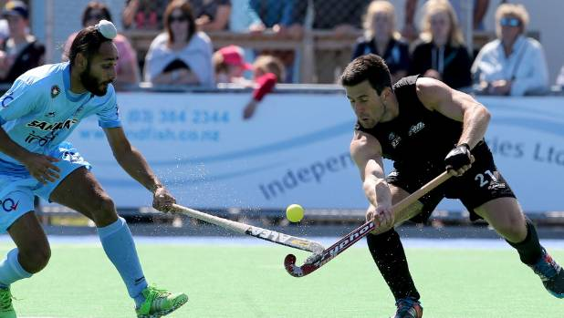 India's Satbir Singh and and New Zealand's Kane Russell tussle for the ball in the drawn men's hockey international at ...