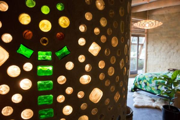 Recycled bottles set within the walls provide colourful diffused light, enlivening the interior.